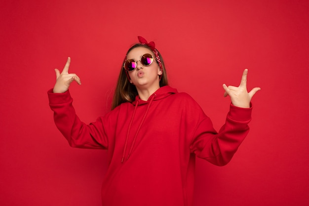 Портрет молодой счастливой позитивной красивой девушки-подростка с искренними эмоциями в красной толстовке с капюшоном и солнцезащитными очками, изолированными на красном фоне с копией пространства и показывающими жест рок-н-ролла.