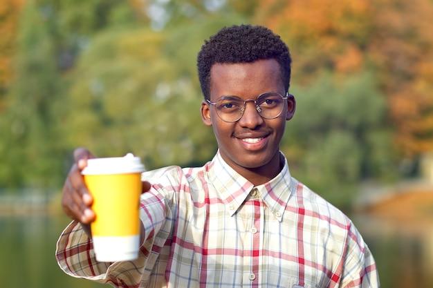 셔츠와 뜨거운 음료 차 또는 커피의 플라스틱 컵을 들고 안경에 젊은 행복 긍정적 인 남자의 초상화 웃 고. 황금가 공원에서 흑인 아프리카 아프리카 계 미국인 남자.