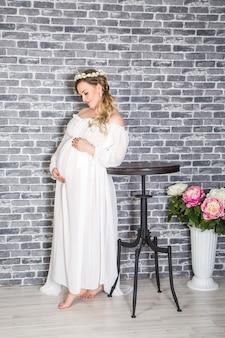 Портрет молодой счастливой беременной женщины, позирующей на кирпичной стене