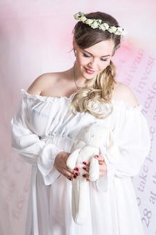 Портрет молодой счастливой беременной женщины, позирующей с плюшевым мишкой