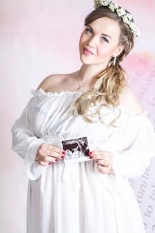 Портрет молодой счастливой беременной женщины с узи своего ребенка