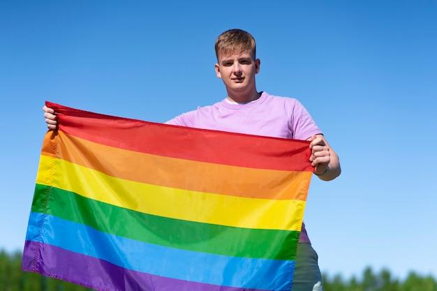 Портрет молодого счастливого гордого гея красивый парень размахивает радужным лгбт-цветным гей-флагом летом