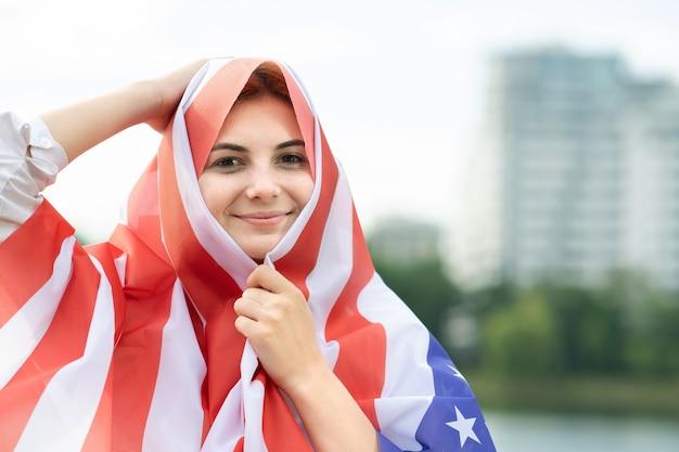 그녀의 머리와 어깨에 미국 국기와 함께 젊은 행복 한 난민 여성의 초상화. 미국 독립 기념일을 축하하는 긍정적인 이슬람 소녀.