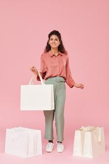 ショッピングバッグの間に立ってピンクの背景に笑みを浮かべて若い幸せな買い物中毒者の肖像画