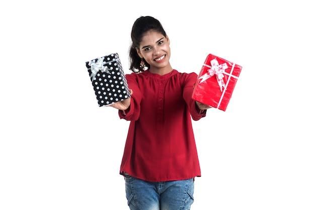 젊은 행복 웃는 여자 잡고 흰색 배경에 선물 상자와 함께 포즈의 초상화.