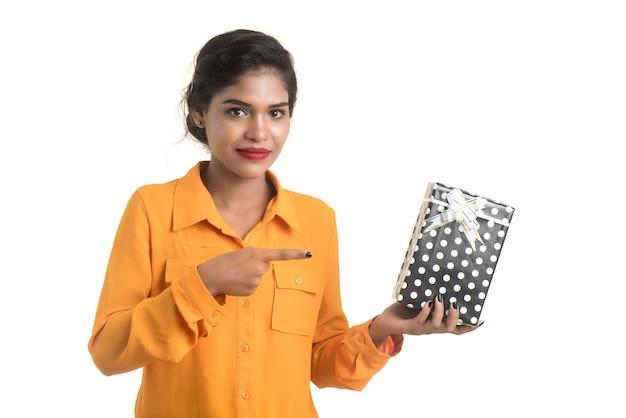 ギフトボックスを保持している若い幸せな笑顔のインドの女の子の肖像画。