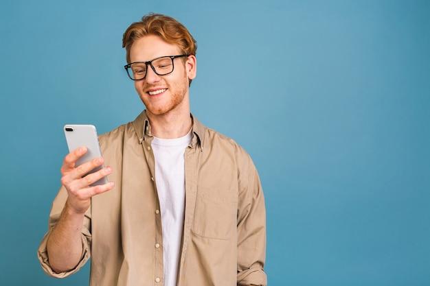 Портрет молодого счастливого улыбающегося человека в случайном вводе sms. используя телефон.