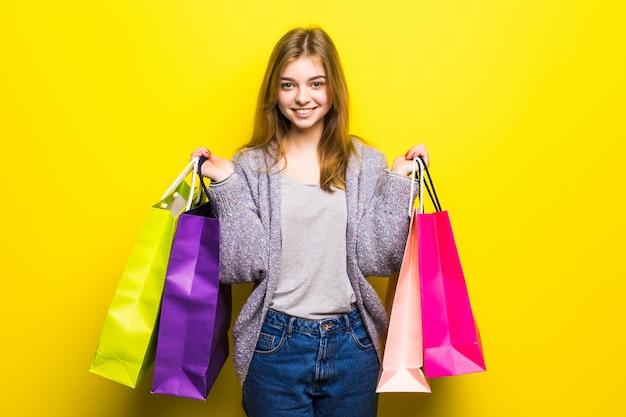 Портрет молодой счастливой улыбающейся девочки-подростка с хозяйственными сумками, изолированные