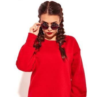밝은 메이크업과 고립 된 여름 빨간 옷에 선글라스 두 땋은 머리와 화려한 입술 젊은 행복 하 게 웃는 여자 모델의 초상화. 패션 선글라스 뒤에