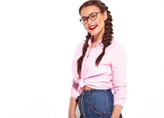 明るいメイクと若い幸せな笑みを浮かべて女性モデルの肖像画と分離された夏のカラフルなピンクの結ばれたシャツの2つのおさげの赤い唇