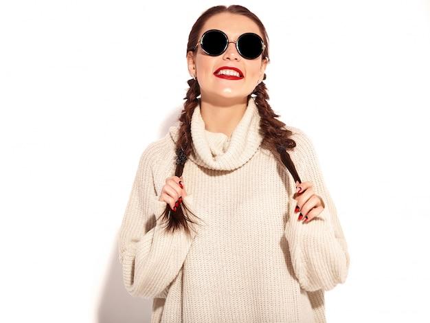 밝은 메이크업과 여름 따뜻한 스웨터 옷 격리에 두 땋은 붉은 입술으로 젊은 행복 하 게 웃는 여자 모델의 초상화.