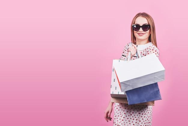 Портрет молодой счастливой улыбающейся женщины с хозяйственными сумками на розовом фоне.
