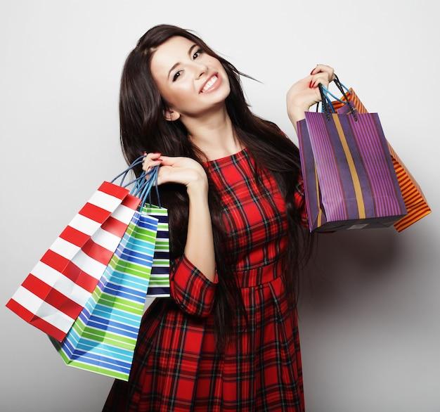 Портрет молодой счастливой улыбающейся женщины с хозяйственными сумками, на белом фоне