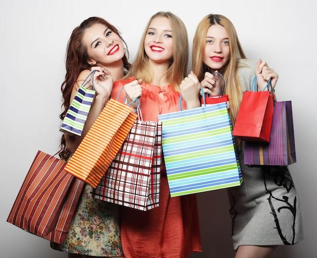 白い壁に買い物袋を持つ幸せな笑顔の若い女性のポートレート