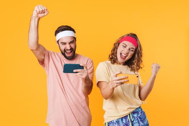 分離された携帯電話を使用しながら喜んでヘッドバンドを身に着けている若い幸せなスポーティなカップルの肖像画