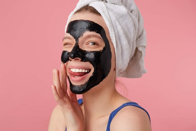 Портрет молодой счастливой женщины после душа с полотенцем на голове, с черной маской, трогает лицо и улыбается, подмигивает и смотрит стоит.