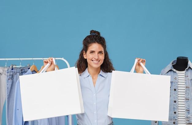 青い背景で隔離の彼女の手で買い物袋を持って服を買う若い幸せな女性の肖像画