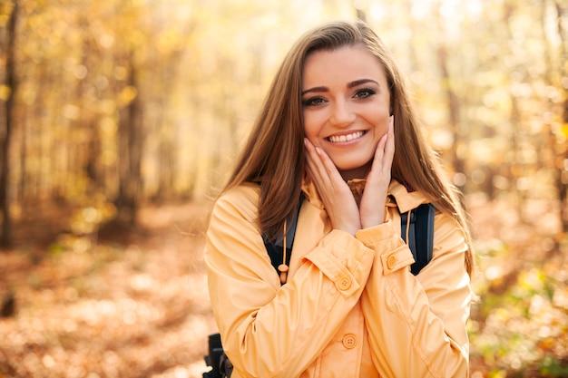 秋のハイキング中の若い幸せな女性の肖像画