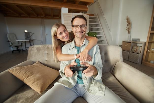 Портрет молодой счастливой женщины, обнимающей своего парня, пока он играет в компьютерную игру, они сидят на диване в гостиной