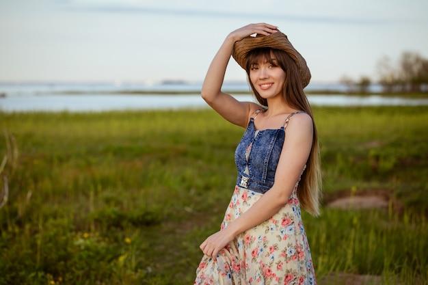 Портрет молодой счастливой женщины в соломенной шляпе на природе у воды