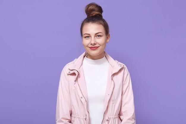 Портрет молодой счастливой женщины изолировал сиреневую стену, одетую в бледно-розовый пиджак и белую рубашку, имеет пучок волос, дама с приятной внешностью.