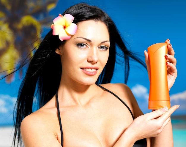 Портрет молодой счастливой женщины на пляже держит оранжевую бутылку лосьона для загара.