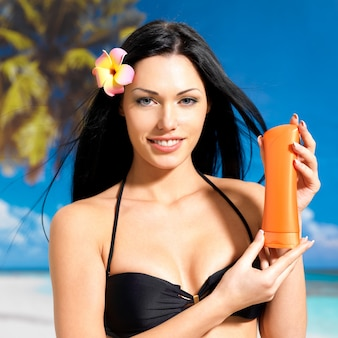 ビーチで若い幸せな女性の肖像画は、オレンジ色の日焼けローションボトルを保持しています。