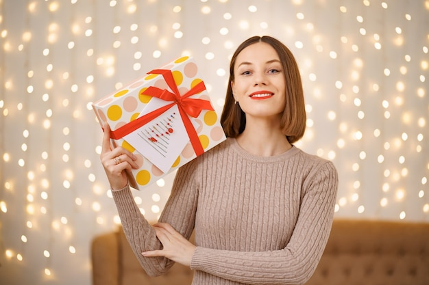 포장 된 선물 상자를 들고 젊은 행복 한 여자 붉은 입술의 초상화.