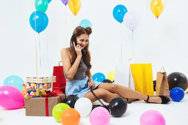 Портрет молодой счастливой женщины разговаривает по телефону, получая пожелания