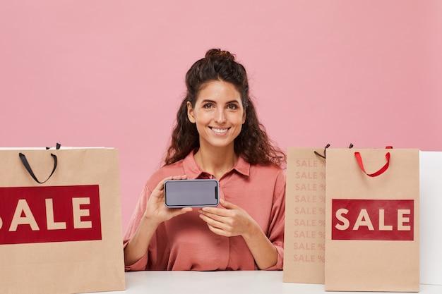 彼女がオンラインで買い物をしている彼女の携帯電話の画面を笑顔で見せている巻き毛の若い幸せな女性の肖像画