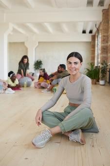 댄스 스튜디오에서 다른 사람들과 함께 바닥에 앉아있는 동안 카메라에 웃고 젊은 건강한 여자의 초상화