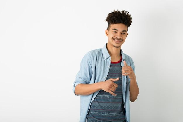 孤立した白いスタジオ壁の背景、スタイリッシュな衣装、面白いアフロの髪型、笑顔、幸せ、クールな男でポーズをとって流行に敏感な若い黒人男性の肖像画
