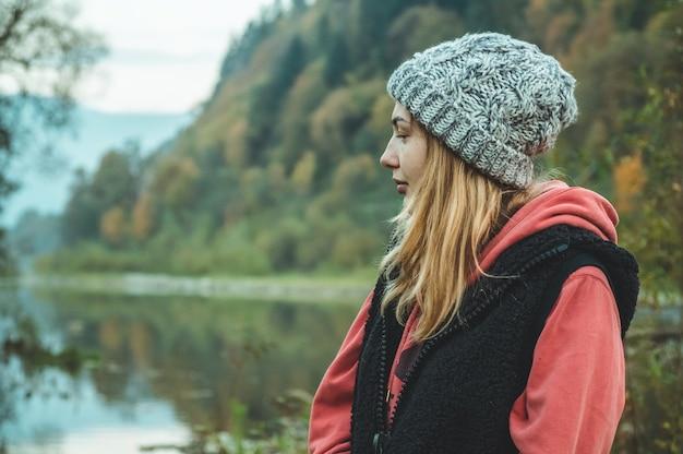 山の素晴らしい景色を楽しんでいる流行に敏感な若い女の子の肖像画、かなり女性の旅行者が空を見て、場所に立っています。