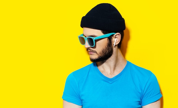 青いシャツを着て、ワイヤレスイヤホンを使用して若い流行に敏感な男の肖像画
