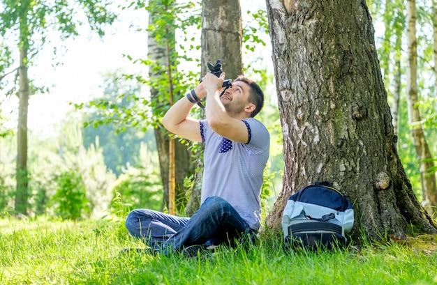 Портрет молодого человека битника с камерой outdoors. молодой мужской фотограф фотографируя природу на летний день.