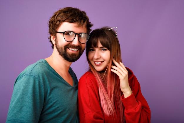 Портрет молодой хипстерской красивой семейной пары в объятиях, в модных повседневных нарядах, парнях и подругах, целях отношений, фиолетовой стене
