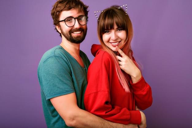 トレンディなカジュアルな服装、ボーイフレンドとガールフレンド、関係の目標、紫の壁を身に着けている若い流行に敏感なかわいい家族のカップルの抱擁の肖像画