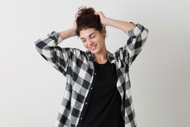 陽気で分離された嬉しいポーズ格子縞のシャツで流行に敏感な若いきれいな女性の肖像画