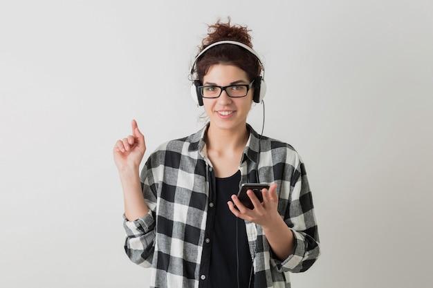 Портрет милой женщины молодого битника усмехаясь в представлять стекел клетчатой рубашки нося изолированный, держащ смартфон и слушающ музыку в наушниках