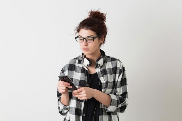 スマートフォンを保持しているポーズをとって眼鏡をかけて市松模様のシャツの若いヒップな笑顔のきれいな女性の肖像画