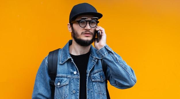 オレンジ色の壁にスマートフォンで話している若いヒップスターの肖像画。ジーンズのジャケット、キャップ、バックパック、眼鏡を着用しています。