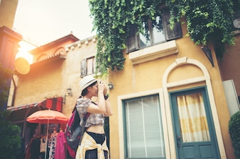 Portrait of young hipster woman backpack traveling taking photo in urban.