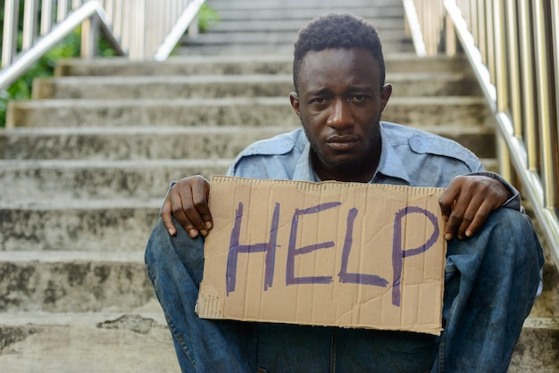 Портрет молодого бездомного африканца на лестнице на улице на открытом воздухе