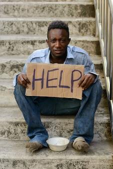 屋外の通りの階段で若いホームレスのアフリカ人の肖像画