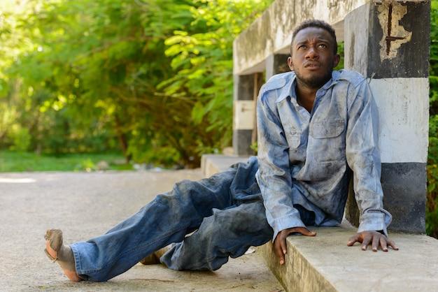 야외 거리에서 다리에 젊은 노숙자 아프리카 남자의 초상화