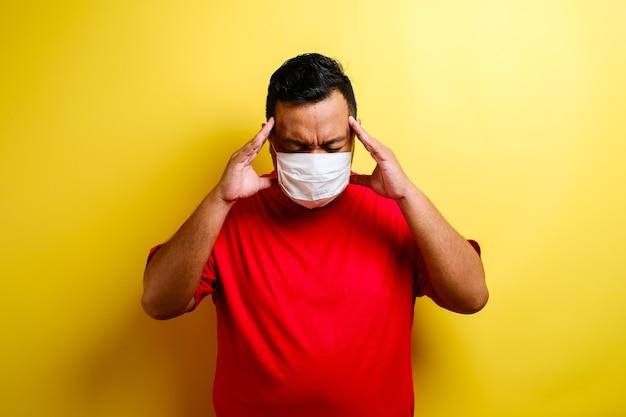 黄色の背景で隔離の頭痛や衰弱に苦しんでいる顔の医療保護マスクで若い病気の男の肖像画