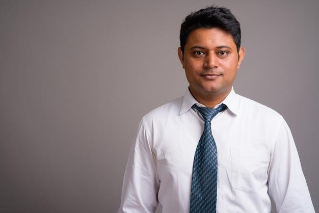 灰色の壁に対する若いインド人実業家の肖像画