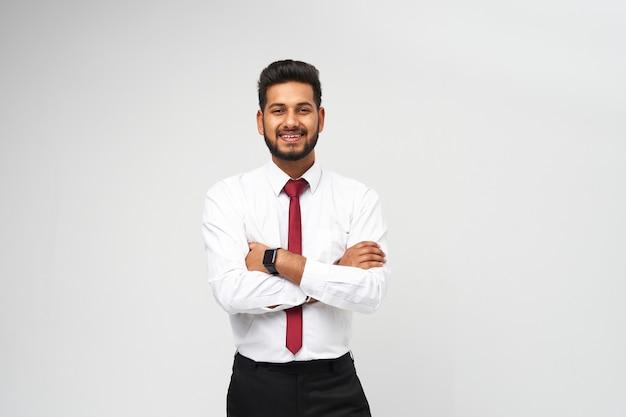 Портрет молодого индийского топ-менеджера в футболке и галстуке, скрестив руки и улыбающегося на белой изолированной стене