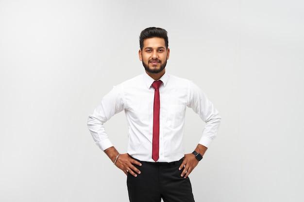 Портрет молодого индийского топ-менеджера в футболке и галстуке на белой изолированной стене