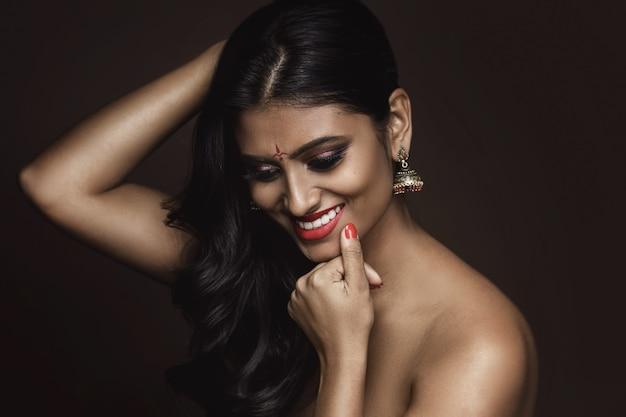 Портрет молодой индийской женщины с красивым макияжем и прической на коричневой стене